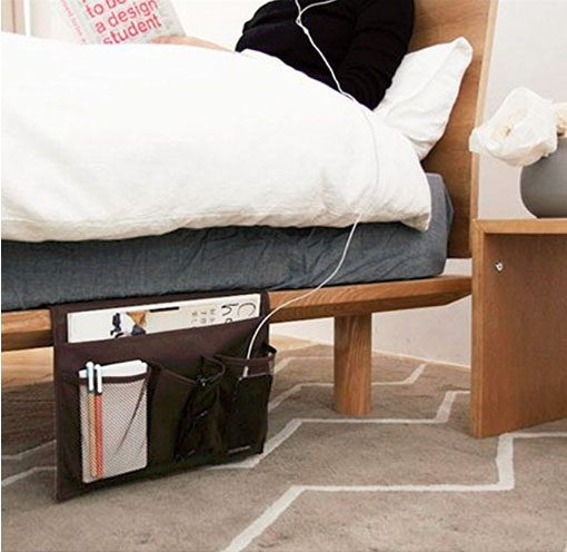 side view of bed with portable hanging caddy holding electronics and nightstand odds and ends as small bedroom organization and storage hack.
