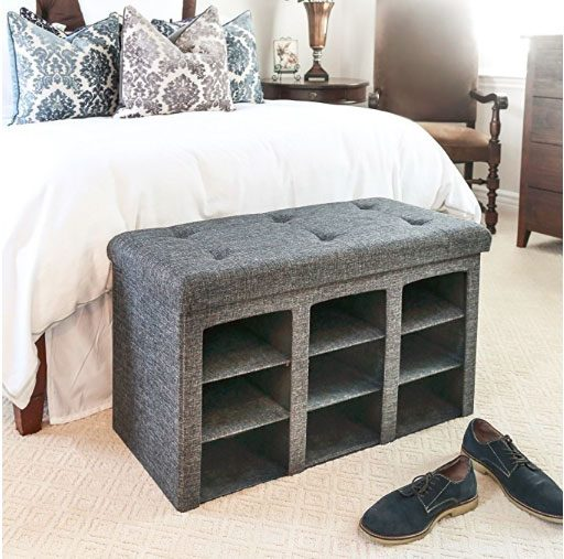 bedroom organization hack by gray ottoman storage bench at foot of bed with side open to reveal compartments to store shoes.